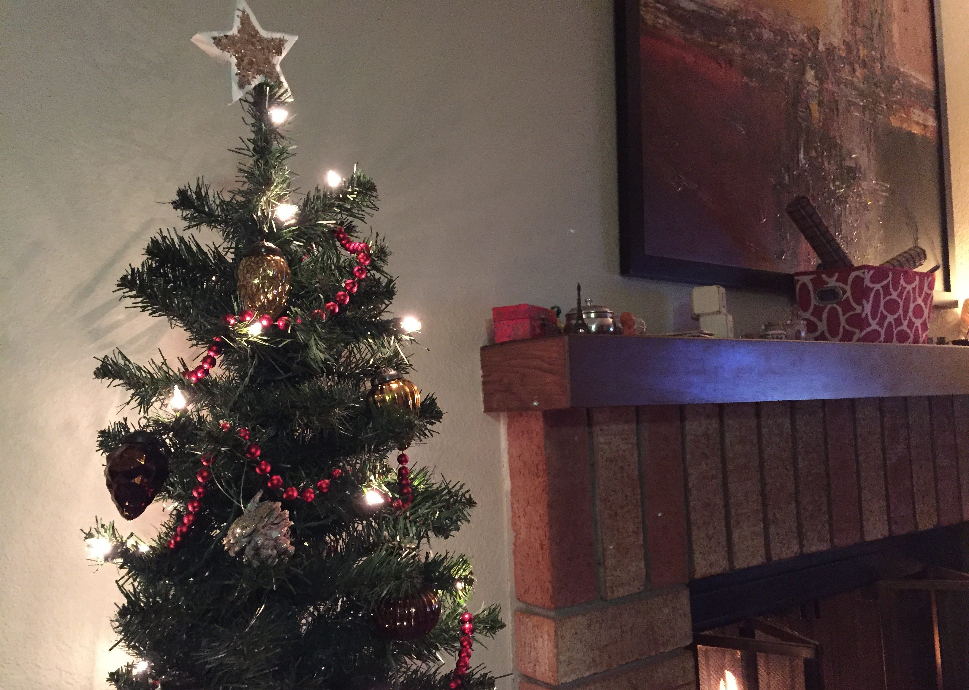 christmas tree by fireplace home for the holidays