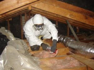 Atticare technician installing attic insulation