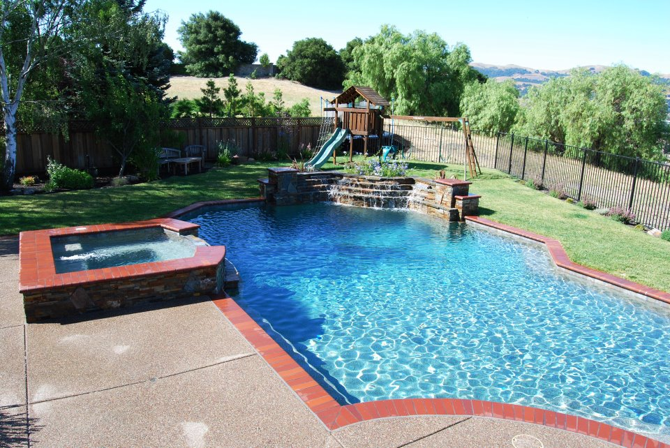 swimming pool with hot tub and waterfall